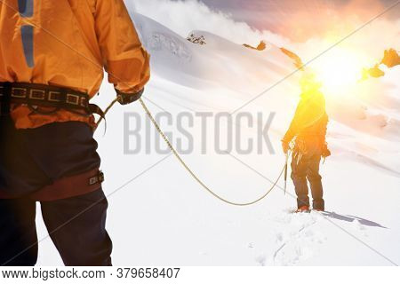 Two mountaineers hiking in mountains holding ropes