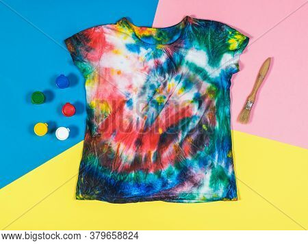 Paint, Brush, And Tie Dye T-shirt On A Three-color Background. White Clothes Painted By Hand. Flat L