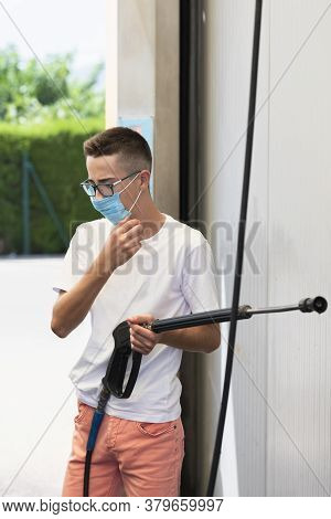 Close Up Of A Young Man Wearing A Face Mask And Glasses Holding A High Pressure Water Spray Wand