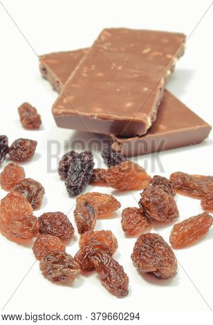Chocolate With Nuts And Raisins On White Background. Delicious Dessert
