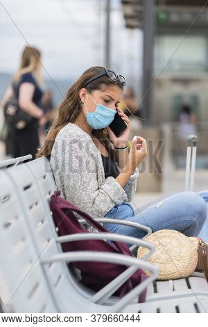Young Woman Wearing A Surgical Mask Talking On Her Phone While Sitting At A Train Station And Keepin