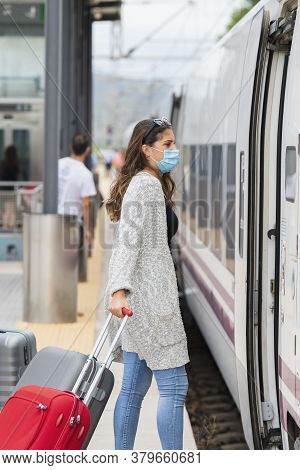Young Woman Wearing A Face Mask And Pulling Suitcases About To Enter A Train At A Train Station