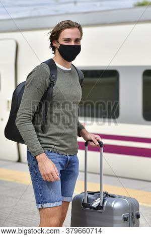 Young Man Wearing A Face Mask And Carrying A Backpack And A Suitcase Waiting At A Train Station