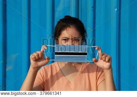 A Woman With Botswana Flag On Hygienic Mask In Her Hand And Lifted Up The Front Face On Blue Backgro