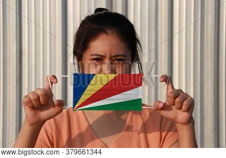 A Woman With Seychelles Flag On Hygienic Mask In Her Hand And Lifted Up The Front Face On Grey Backg
