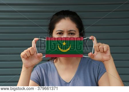 A Woman With Mauritania Flag On Hygienic Mask In Her Hand And Lifted Up The Front Face On Dark Green