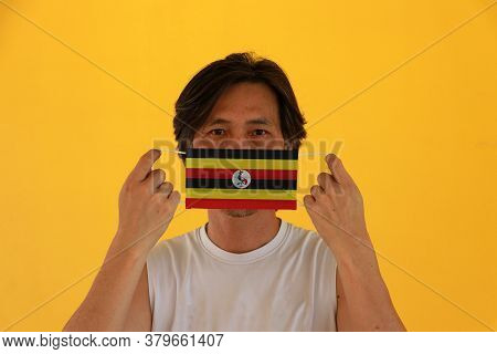 A Man With Uganda Flag On Hygienic Mask In His Hand And Lifted Up The Front Face On Yellow Backgroun