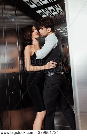 Selective Focus Of Man In Waistcoat Touching Neck Of Beautiful Woman In Dress In Elevator