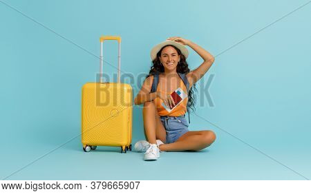 Go on an adventure! Happy woman going traveling. Young person with suitcase on color teal background.