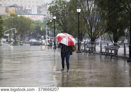 Bronx, New York/usa - September 25, 2018: Woman Walks With Umbrella In Rain Near Yankee Stadium.