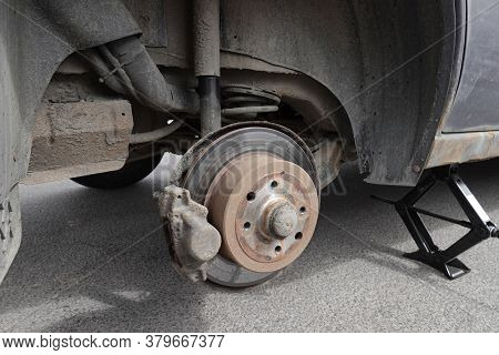 An Old Car With A Removed Wheel On The Jack
