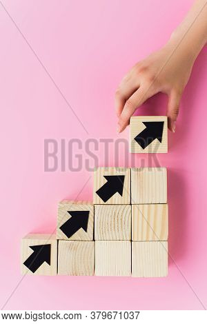 Partial View Of Hand Near Wooden Blocks With Black Arrows On Pink Background, Business Concept
