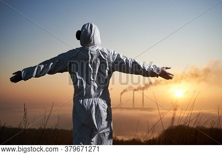 Back View Of Scientist In Protective Suit Looking At Blue Sky Over Thermal Power Plant. Male Environ