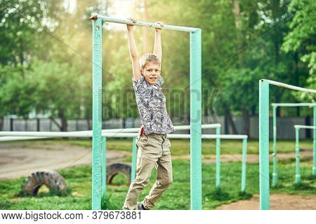 Strong Kid Doing Pull Ups On Sports Ground