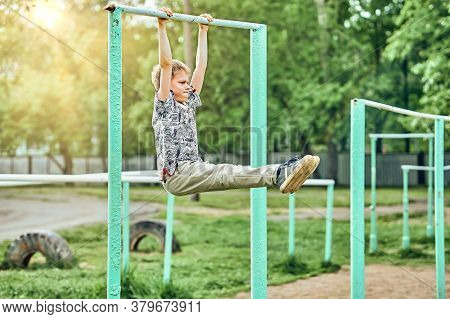 Strong Kid Doing Hanging L-sit On Sports Ground