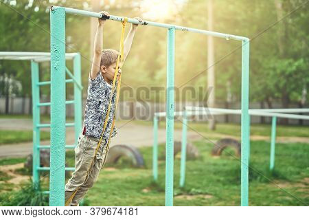 Strong Kid Doing Doing Exercises With A Fitness Elastic Band On Sports Ground