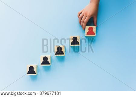 Partial View Of Hand And Wooden Blocks With Black And Red Human Icons On Blue Background, Leadership