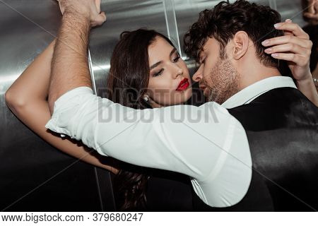 Man In Shirt And Waistcoat Near Attractive Woman With Red Lips In Elevator