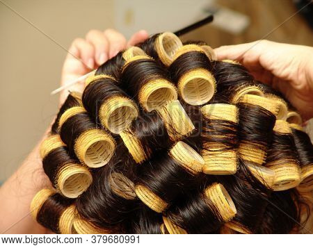 curly woman doing her hair at hairdresser with Velcro rollers
