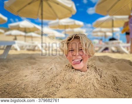 Portrait Of Handsome Teen Blond Boy With Forelock Buried Himself In The Sand On The Beach. Sunshades