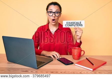 Young brunette woman using laptop holding exascale computers banner scared and amazed with open mouth for surprise, disbelief face