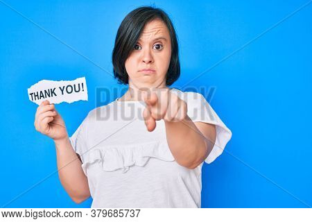 Brunette woman with down syndrome holding thank you paper pointing with finger to the camera and to you, confident gesture looking serious