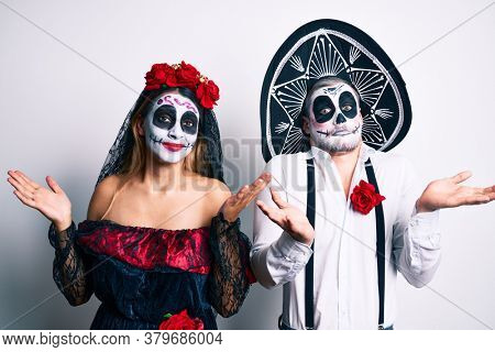 Couple wearing day of the dead costume over white clueless and confused with open arms, no idea and doubtful face.