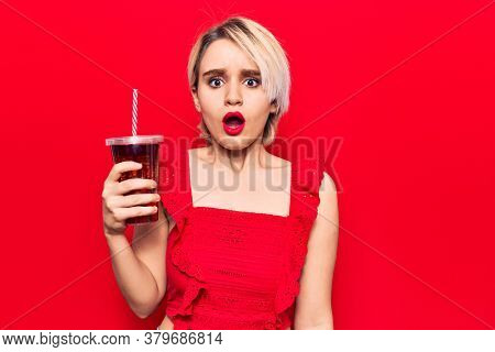 Young beautiful blonde woman drinking glass of cola beverage scared and amazed with open mouth for surprise, disbelief face