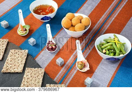 Selection Of Asian Appetiser In A Chinese Service Bowls And Ceramic Spoons With Decorated Table