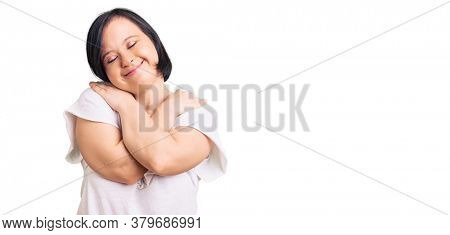 Brunette woman with down syndrome wearing casual white tshirt hugging oneself happy and positive, smiling confident. self love and self care
