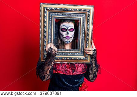 Young woman wearing day of the dead costume holding empty frame annoyed and frustrated shouting with anger, yelling crazy with anger and hand raised