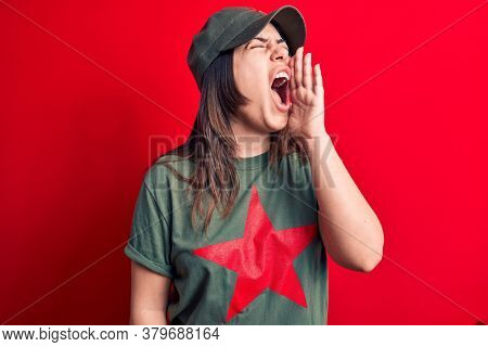 Young beautiful brunette woman wearing cap and t-shirt with red star communist symbol shouting and screaming loud to side with hand on mouth. Communication concept.