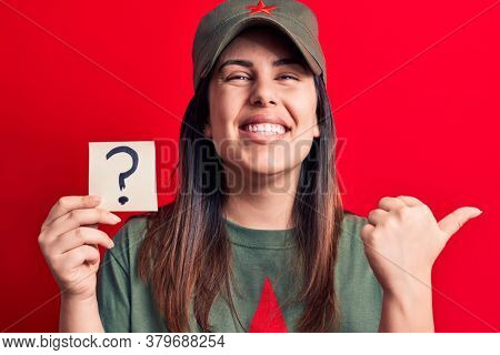 Beautiful woman wearing cap with red star communist symbol holding question mark reminder pointing thumb up to the side smiling happy with open mouth