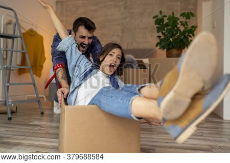 Young Couple In Love Moving In Together, Having Fun While Unpacking Cardboard Boxes With Their Belon