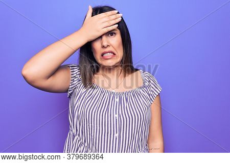 Young beautiful brunette woman wearing casual striped t-shirt standing over purple background surprised with hand on head for mistake, remember error. Forgot, bad memory concept.