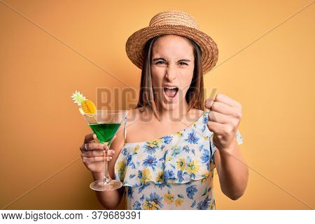 Young beautiful tourist woman on vacation wearing summer hat drinking cocktail beverage annoyed and frustrated shouting with anger, crazy and yelling with raised hand, anger concept