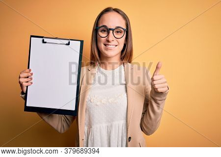 Beautiful inspector woman wearing glasses holding checklist clipboard over yellow background happy with big smile doing ok sign, thumb up with fingers, excellent sign
