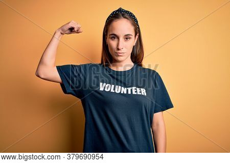 Young beautiful woman wearing volunteer t-shirt doing volunteering over yellow background Strong person showing arm muscle, confident and proud of power