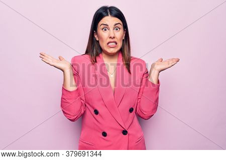 Young beautiful business woman wearing elegant jacket standing over pink background clueless and confused with open arms, no idea and doubtful face.