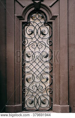 A Window With A Metal Grille With Patterns With A Lilac Sheen.