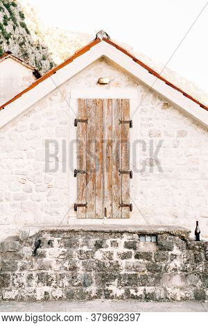 Old Wooden Door To The Attic In A White Wall With An Orange Roof.