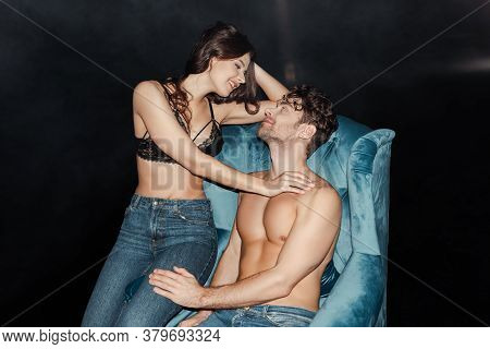 Smiling Woman In Bra And Jeans Touching Shirtless Boyfriend On Armchair On Black