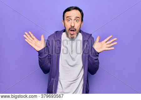 Middle age handsome sporty man wearing casual purple sweatshirt over isolated background clueless and confused with open arms, no idea and doubtful face.