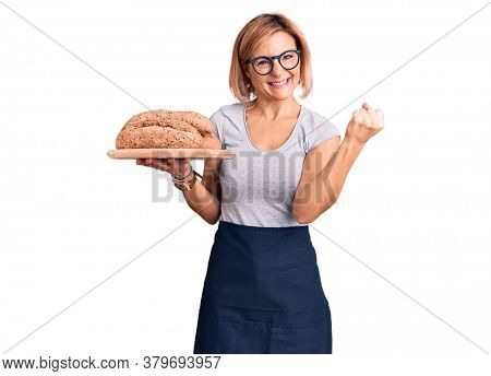 Young blonde woman holding wholemeal bread screaming proud, celebrating victory and success very excited with raised arms