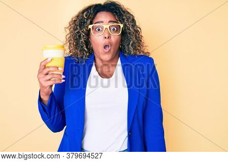 Young african american plus size woman wearing glasses holding take away cup of coffee scared and amazed with open mouth for surprise, disbelief face