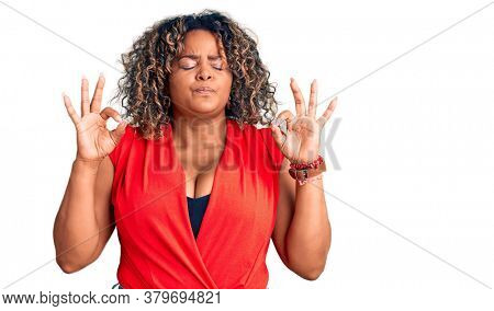Young african american plus size woman wearing casual style with sleeveless shirt relaxed and smiling with eyes closed doing meditation gesture with fingers. yoga concept.