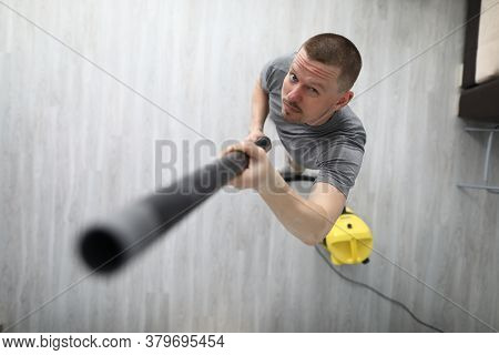 A Man Collects Dust From The Ceiling With A Vacuum Cleaner. The Tool Sucks In Dust And Debris On The
