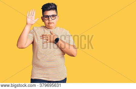 Little boy kid wearing casual clothes and glasses swearing with hand on chest and open palm, making a loyalty promise oath