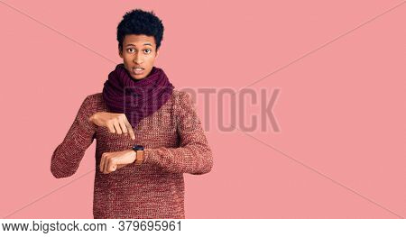 Young african american man wearing casual winter sweater and scarf in hurry pointing to watch time, impatience, upset and angry for deadline delay