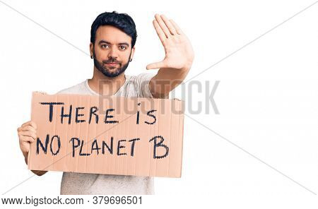 Young hispanic man holding there is no planet b banner with open hand doing stop sign with serious and confident expression, defense gesture